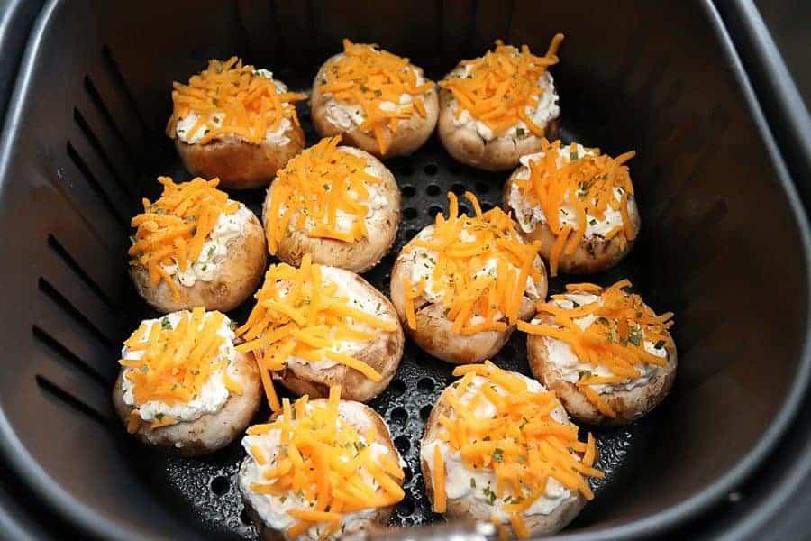 Air fryer basket with uncooked prepared stuffed mushrooms