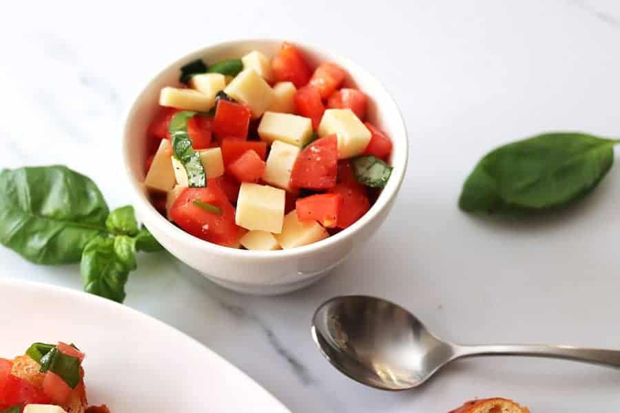 Diced tomato, basil leaves, and diced mozzarella in a cup with a spoon next to it