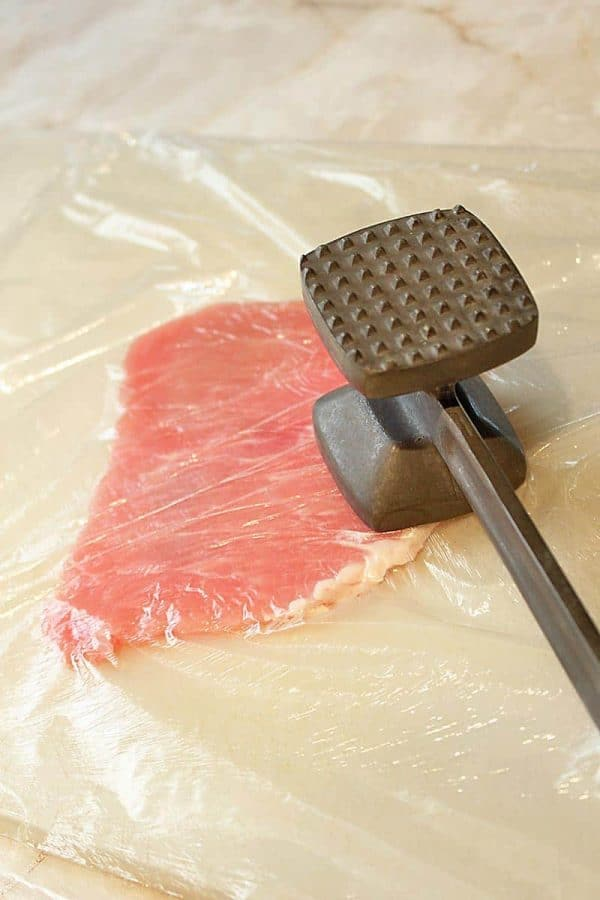 Tenderizing the pork with a mallet