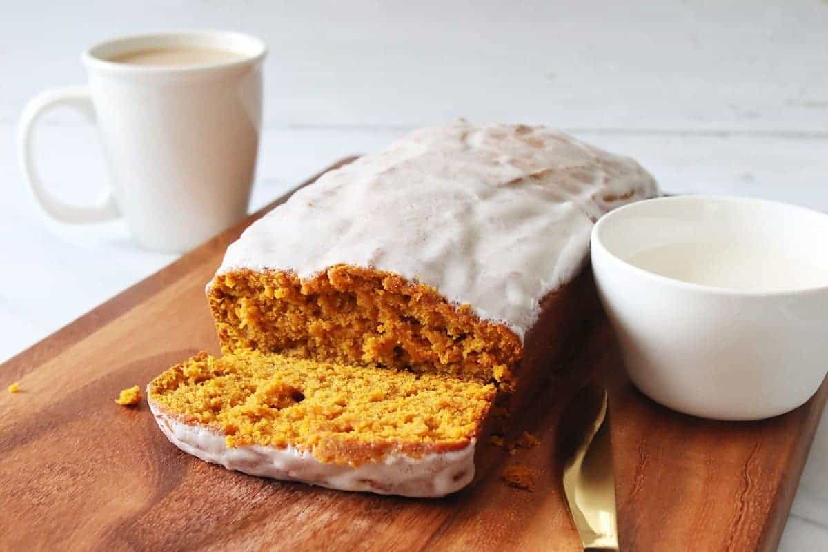 Iced Pumpkin Bread with coffee and cup of icing