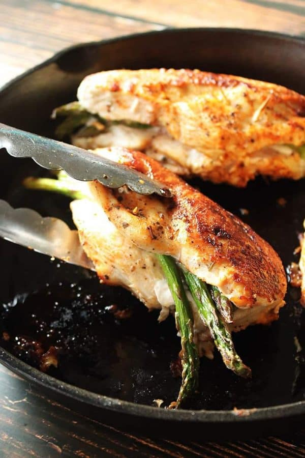 Tongs picking up chicken breast in cast-iron skillet