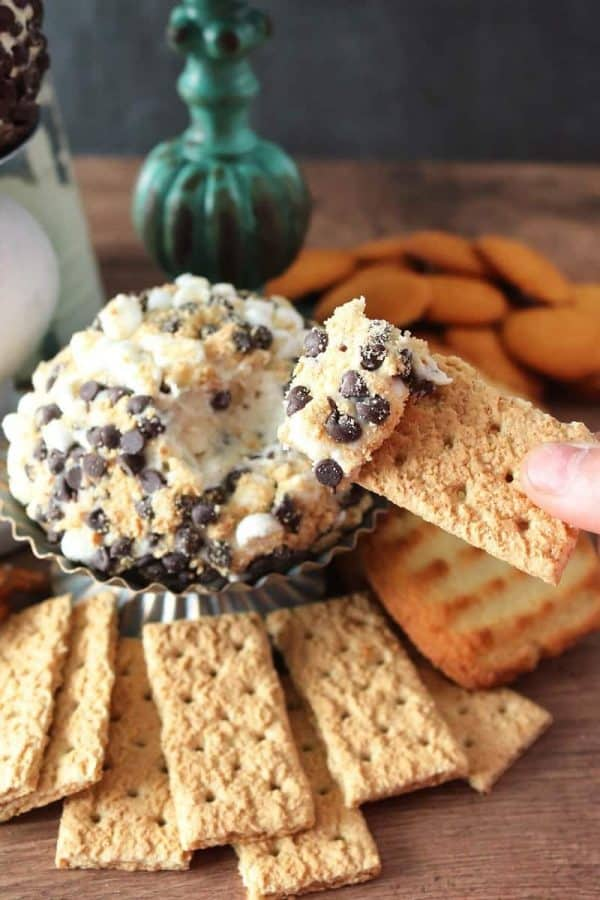 Dipping a graham cracker into a chocolate chip cookie dough cheese ball
