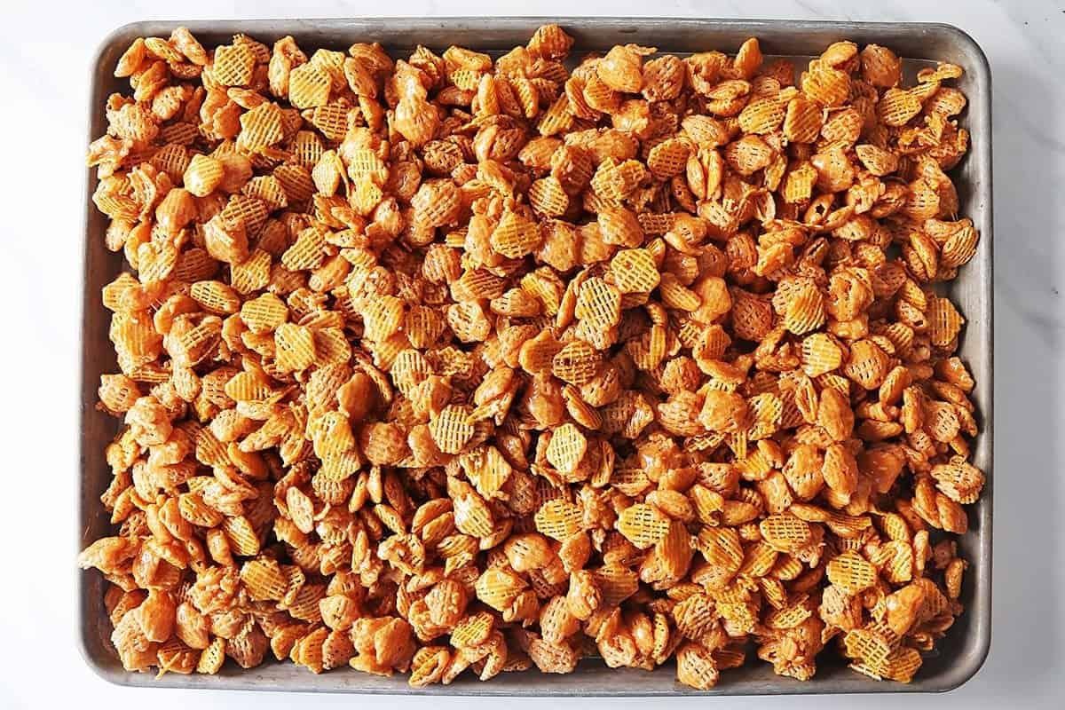 Caramel Crispix spread out on a baking sheet