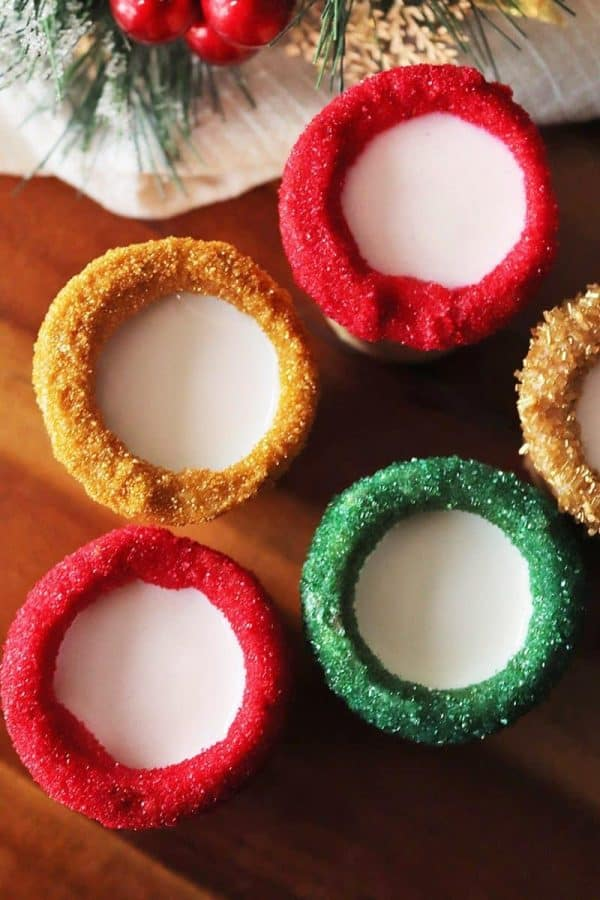 Sugar cookie shots with red, green, and gold sugar on the rims and milk inside