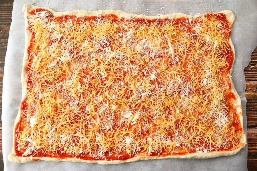 Pizza dough with pizza sauce sprinkled with cheddar and mozzarella cheese