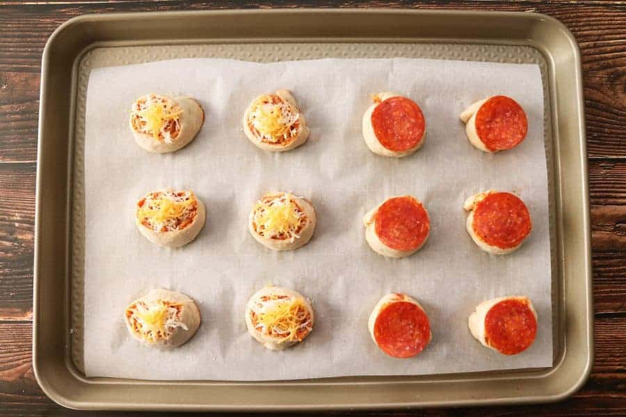 A cookie sheet lined with 6 cheese pizza roll-ups and 6 pepperoni pizza roll-ups