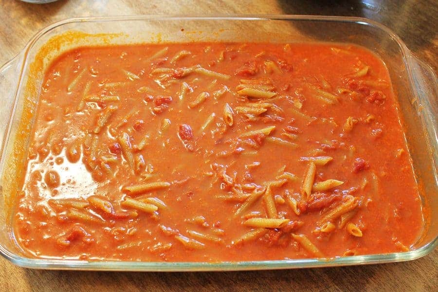 Penne mixed with pasta sauce in a baking dish