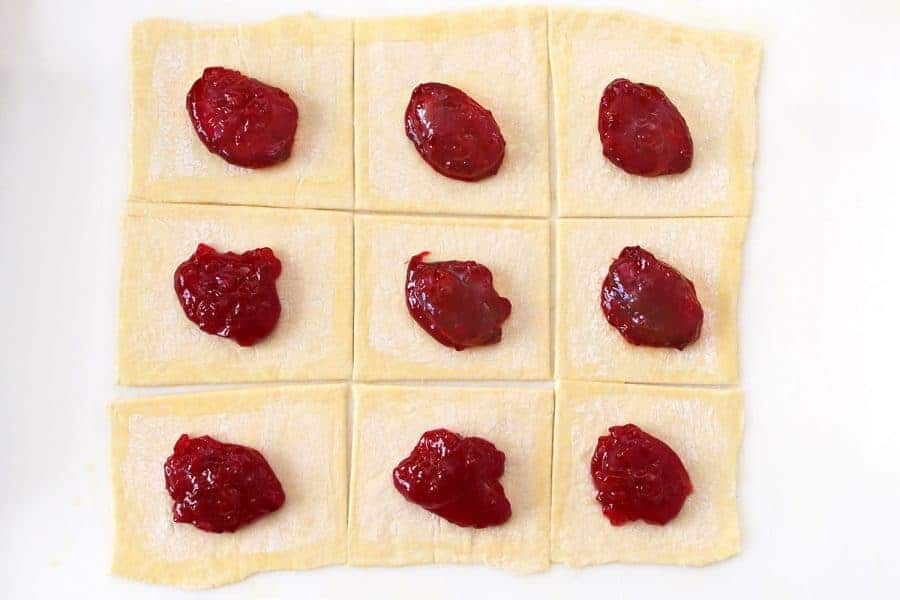 Rolled out puff pastry dough with cherry filling on each square