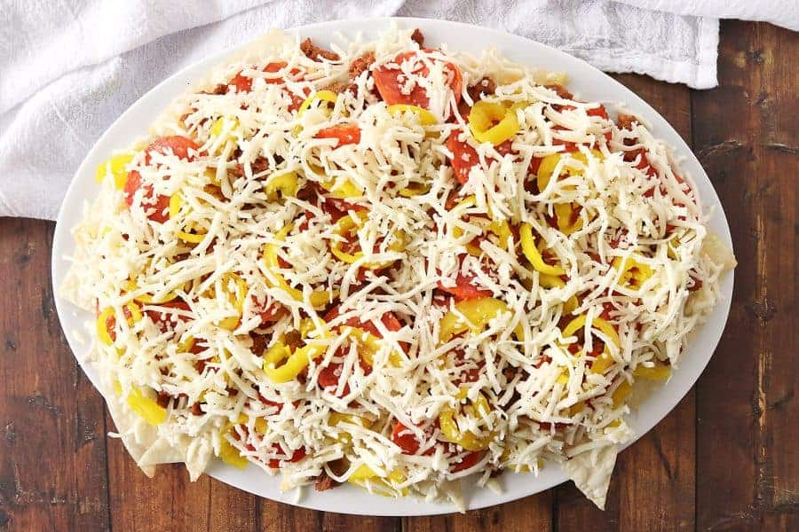 The unbaked version of the Italian nachos with mozzarella cheese on top