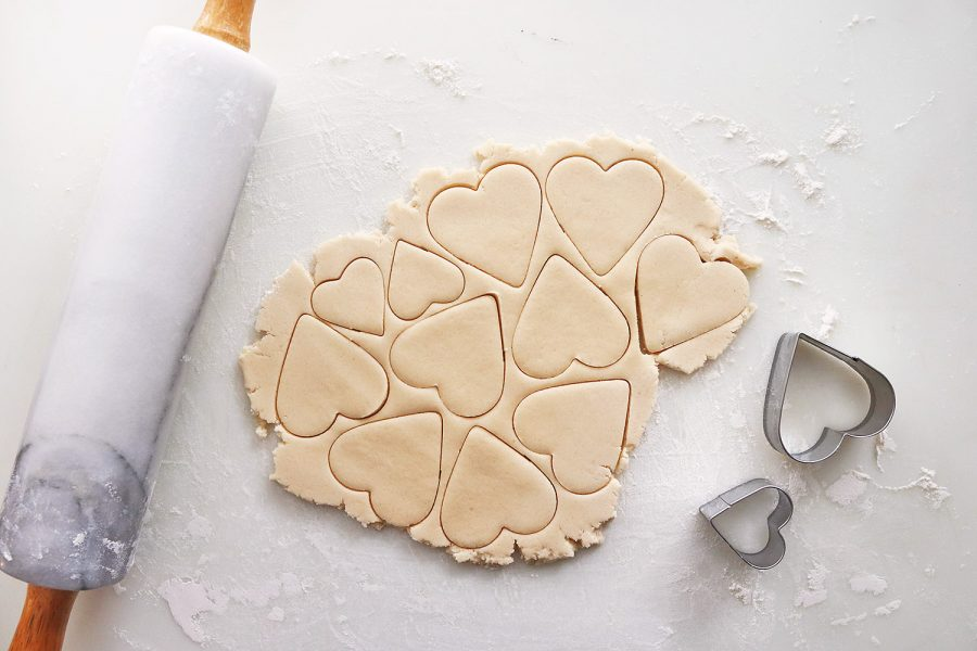 Butter cookie dough rolled out with a rolling pin and cut into heart shapes