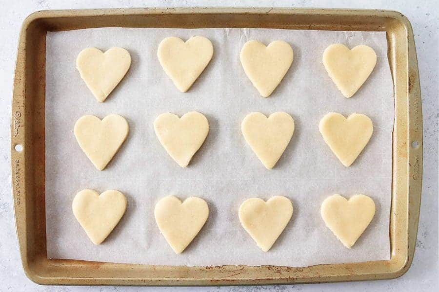 Unbaked heart-shaped cookies on a baking sheet